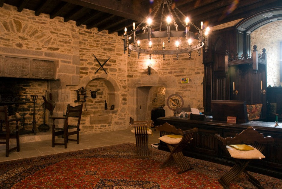 A living and dining area inside of a castle themed room, with authentic stone walls and large stone fireplace