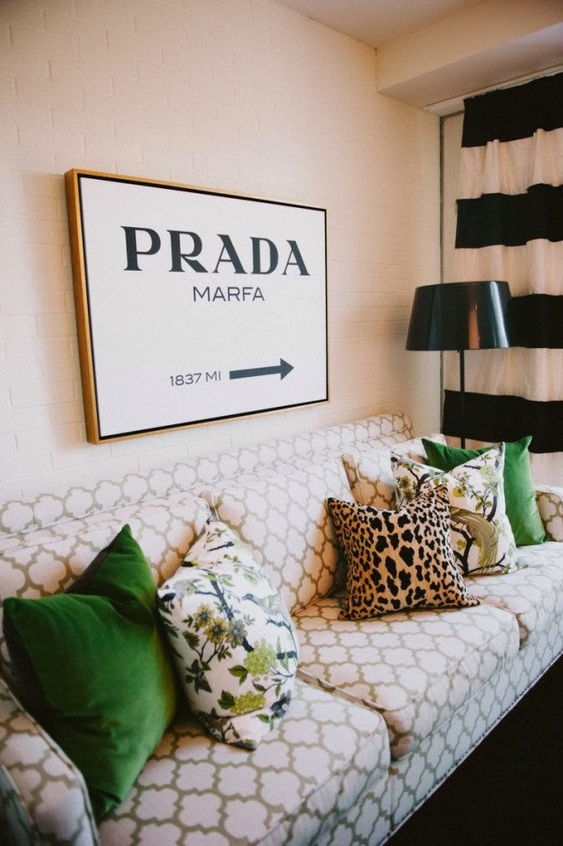 Geometric patterned sofa in white and cream and Prada canvas hung on the wall
