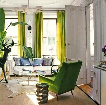 A white and light green living room with green curtains and green armchair