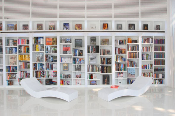 White modular bookshelves in a white reading room, with funky chaise lounges for reading on
