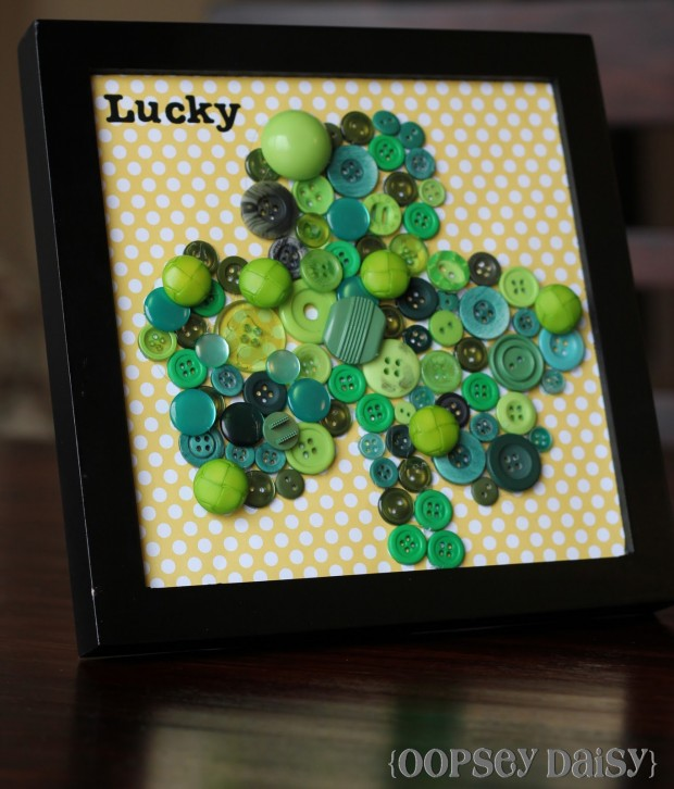 A homemade black picture frame containing a clover made from green buttons