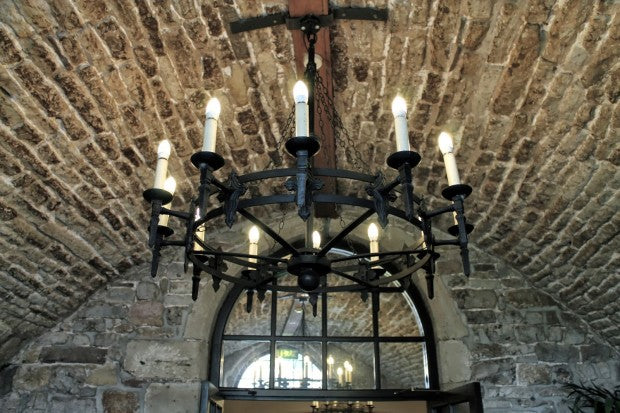 Curved stone ceiling with black candle chandelier