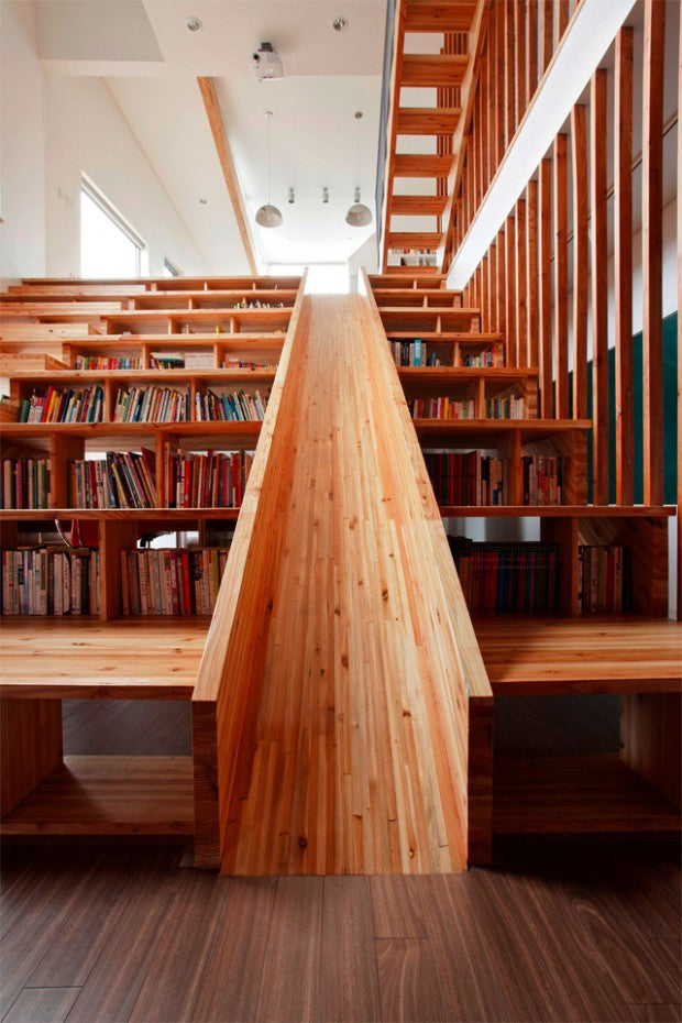 Very wide wooden staircase and sitting area, with a slide down the middle and book storage under each step