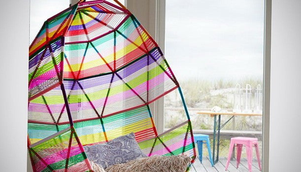 A funky rainbow coloured pod chair, looking out onto garden decking