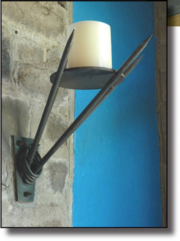 Wall mounted candle on a black lead spike, mounted on a stone wall