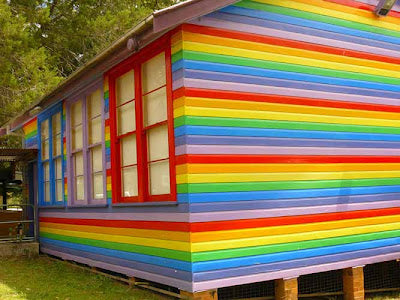 A summer house with wooden panels painting in different colours made to look like a rainbow
