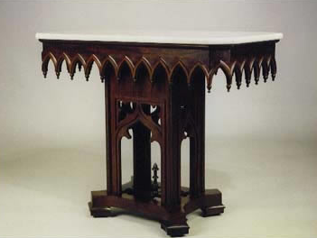 A dark wooden table with an ornate Gothic design