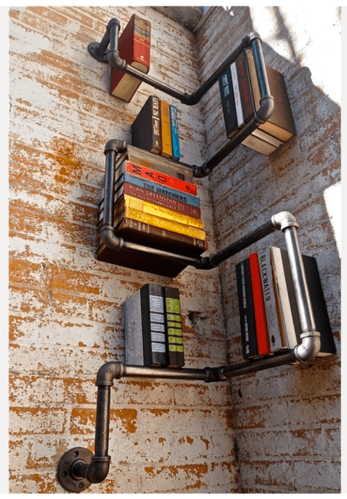 Black metal pipes meandering in the corner of a room, creating space for book storage