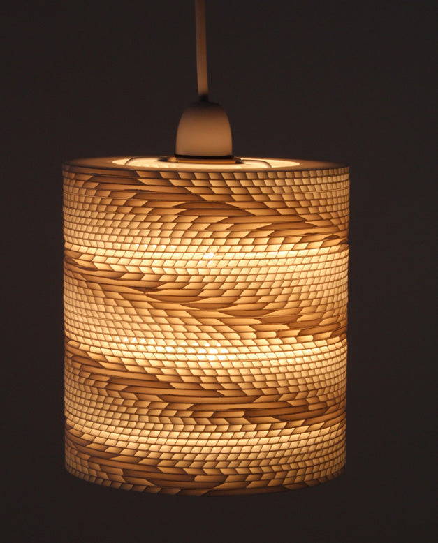 A cream and beige lamp shade that is a cylinder but has a texture reminiscence of a car tyre