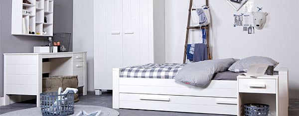 White and light grey bedroom with white bed, with drawers underneath