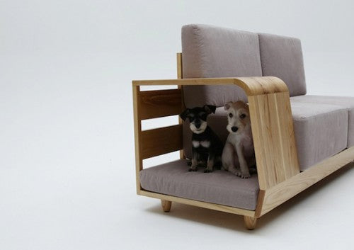 Dog bed at the side of beige sofa, enclosed in wooden frame