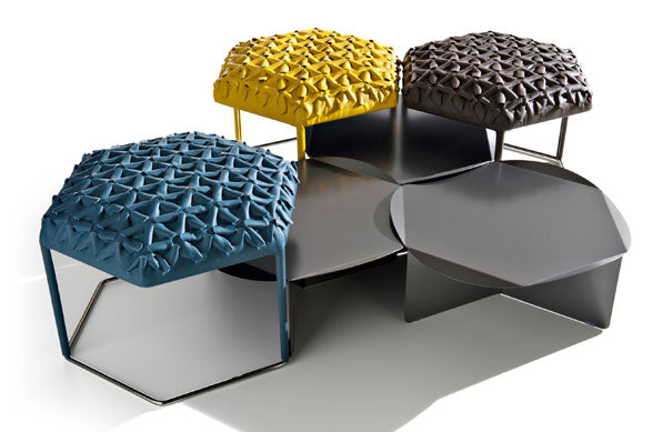 Hexagonal seats in blue, yellow and black that have a textured design that look like starfish holding hands