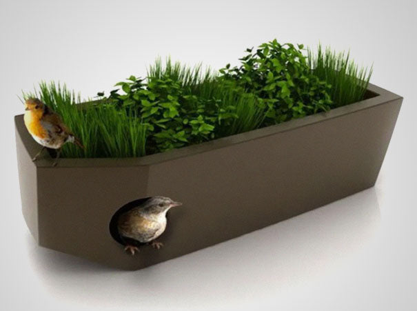 Brown rectangular planter with greenery growing, with a birdhouse inside