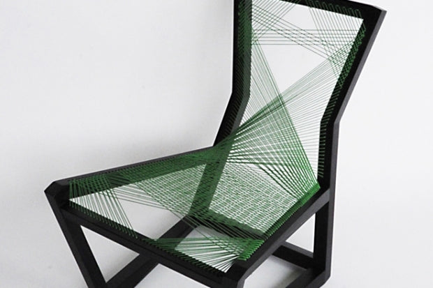 A black chair frame in an irregular shape, with a woven green cord used to making a seat and back rest