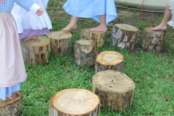 Children hopping over log stumps, using them as stepping stones