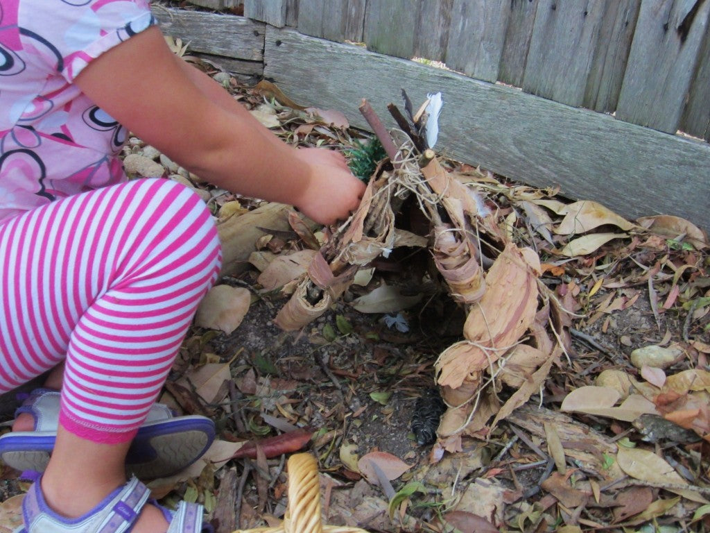 A child playing with leaves in the garden