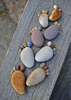 Stones arranged on a wooden beam that looks like feet