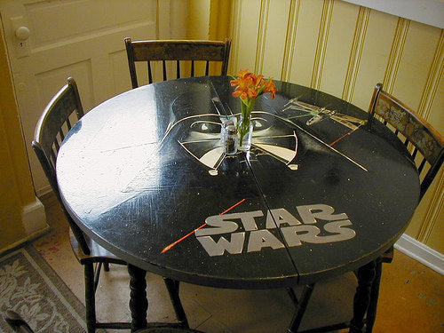 Black round dining room table with a Darth Vader and X-wing design on it