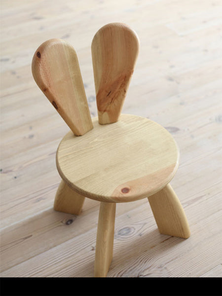 Wooden tripod stool with a back support in the shape of bunny ears