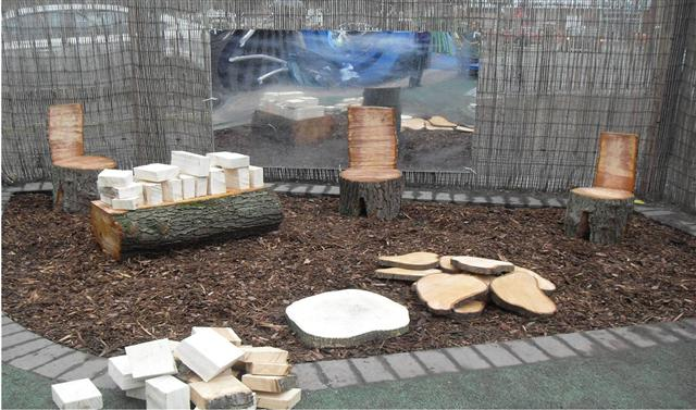A fun garden play area for kids, with bark flooring and tree stump chairs