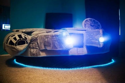 A Millennium Falcon kids bed with trail of blue fairy lights