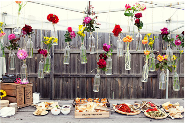 Red, Yellow And Pink Flowers In Bottles Hanging Inside A Gazebo