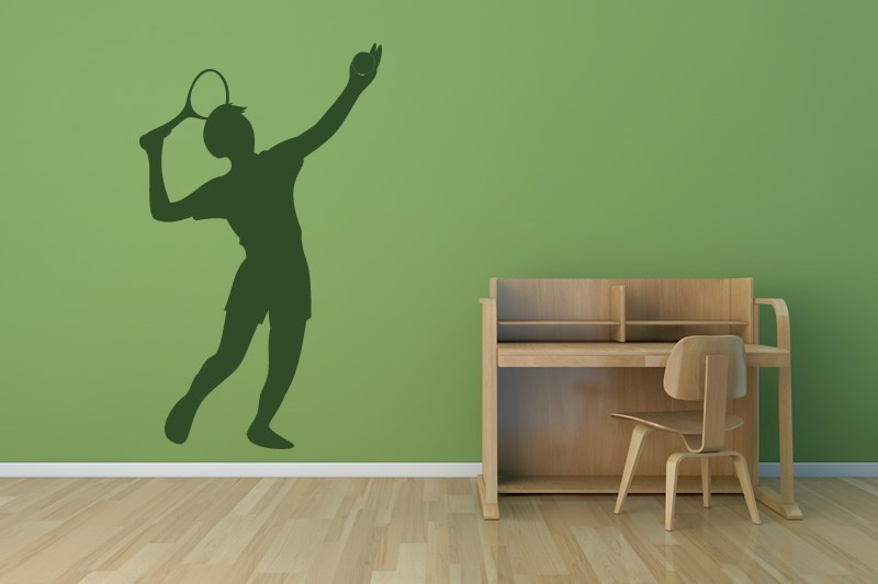A green wall with a dark green decal of a person serving a tennis ball