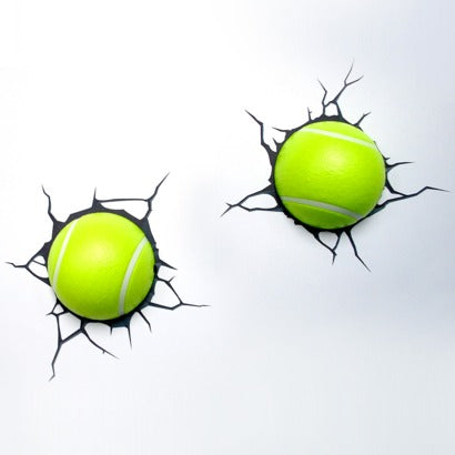 White wall with black cracked decal and tennis balls stuck on the decal, made to look like the ball has been hit against the wall and caused a crack