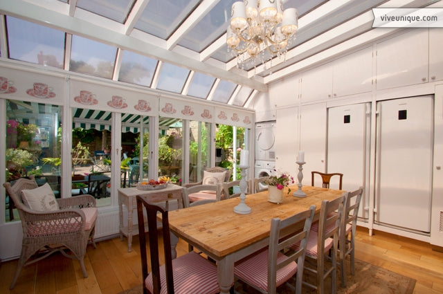 Large white conservatory overlooking a garden, used as a dining room with light pink chairs and accessories