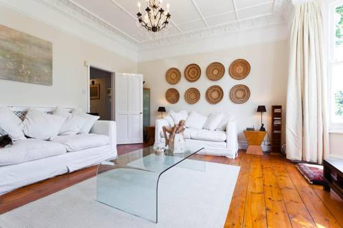 Large white living room with white sofa and stained wooden floors