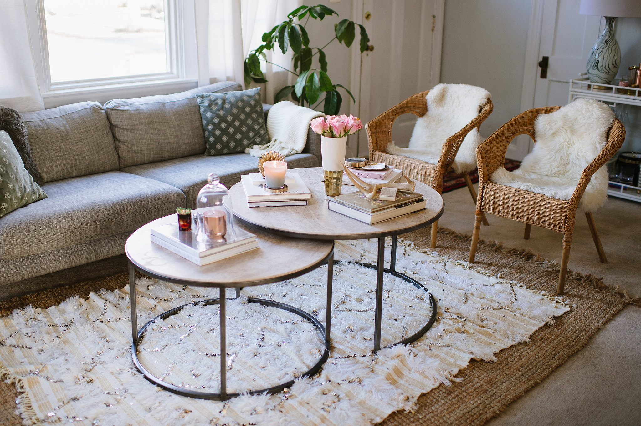 Two Ratan Chairs, Grey Sofa And Two Round Coffee Tables On A White Rug