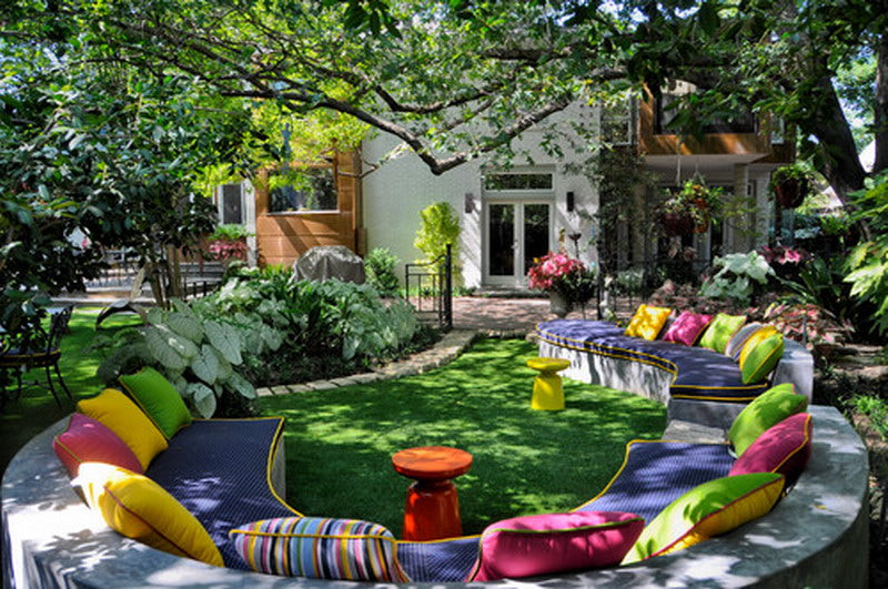 A Round Seating Area In A Garden, Covered In Cushions And Seatpads