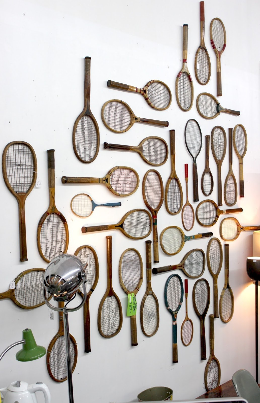 A selection of tennis rackets hung on a white wall