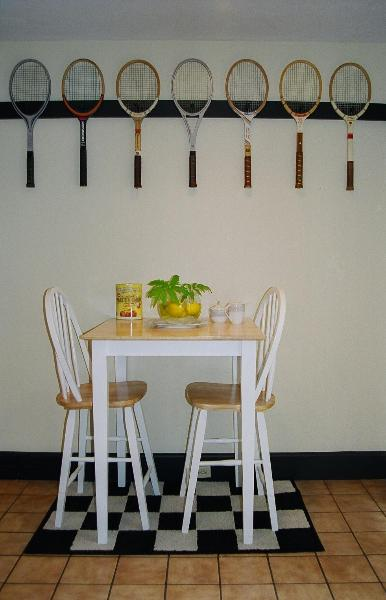 A row of tennis rackets hung to the wall above a small dining table