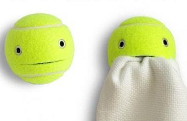 A tennis ball with a cut in it, which is holding a towel