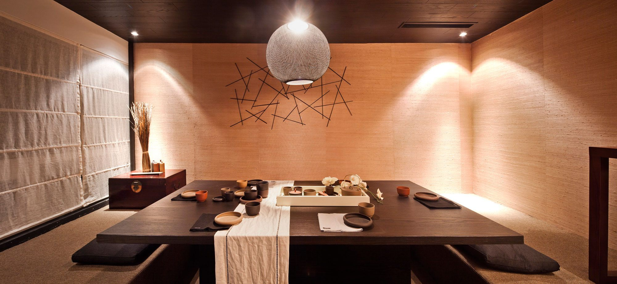 Beige dining room with brown table, that is shaped like a booth where you slide in, like at a diner