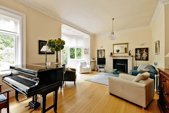 Light wooden floor with cream walls in a living room, and black grand piano in the corner of the room