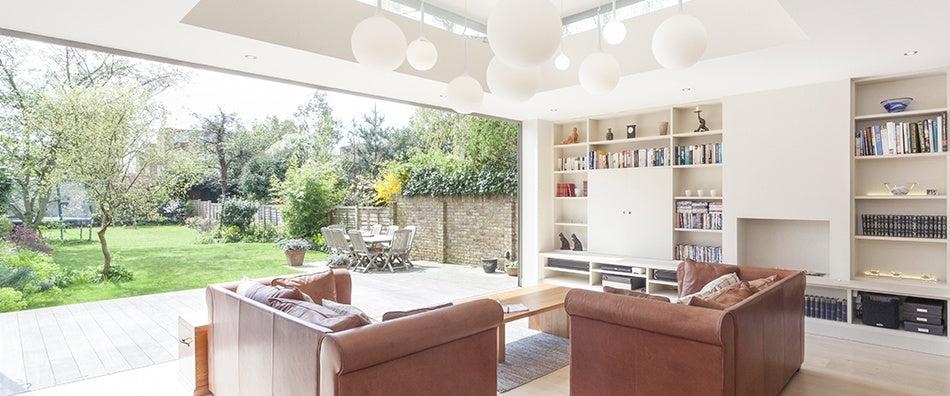 Cream living room with slide away glass wall, that fully connects with the stunning large garden