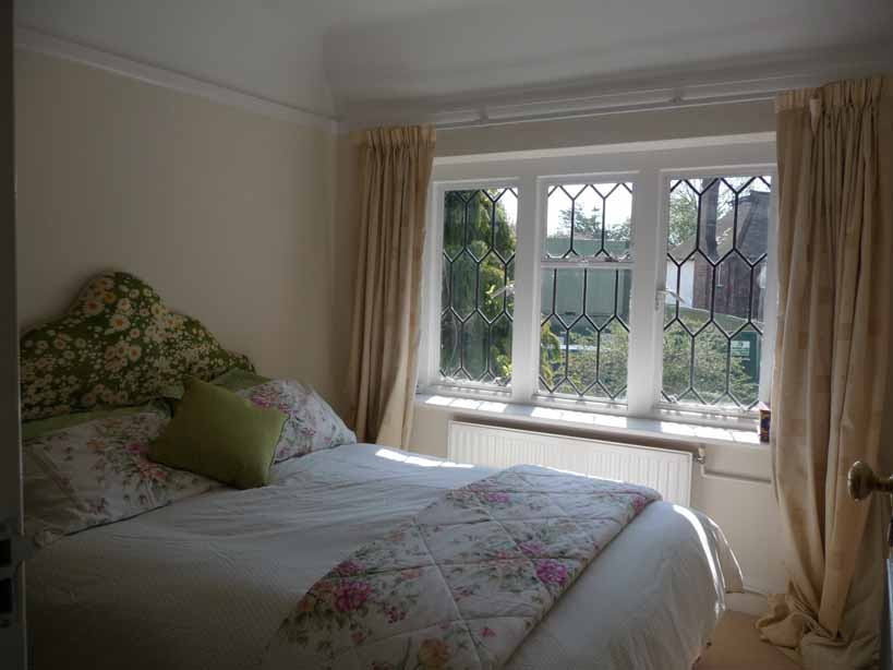 Poorly lit bedroom with cream walls and curtains and white and floral bedding