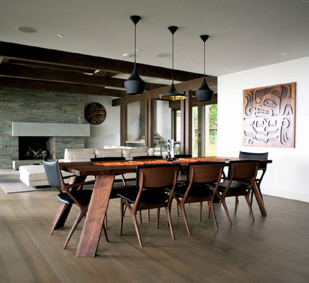 Large dark wooden beam living space with cream sofas in the distance and wooden dining table in the foreground