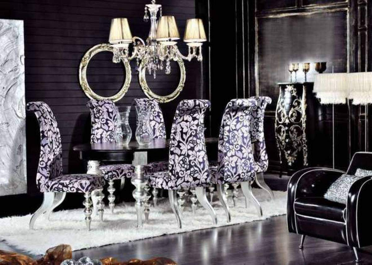 Black dining room, with black table and black and lilac padded chairs