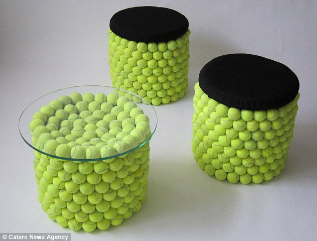 Glass topped table with a base made from tennis balls