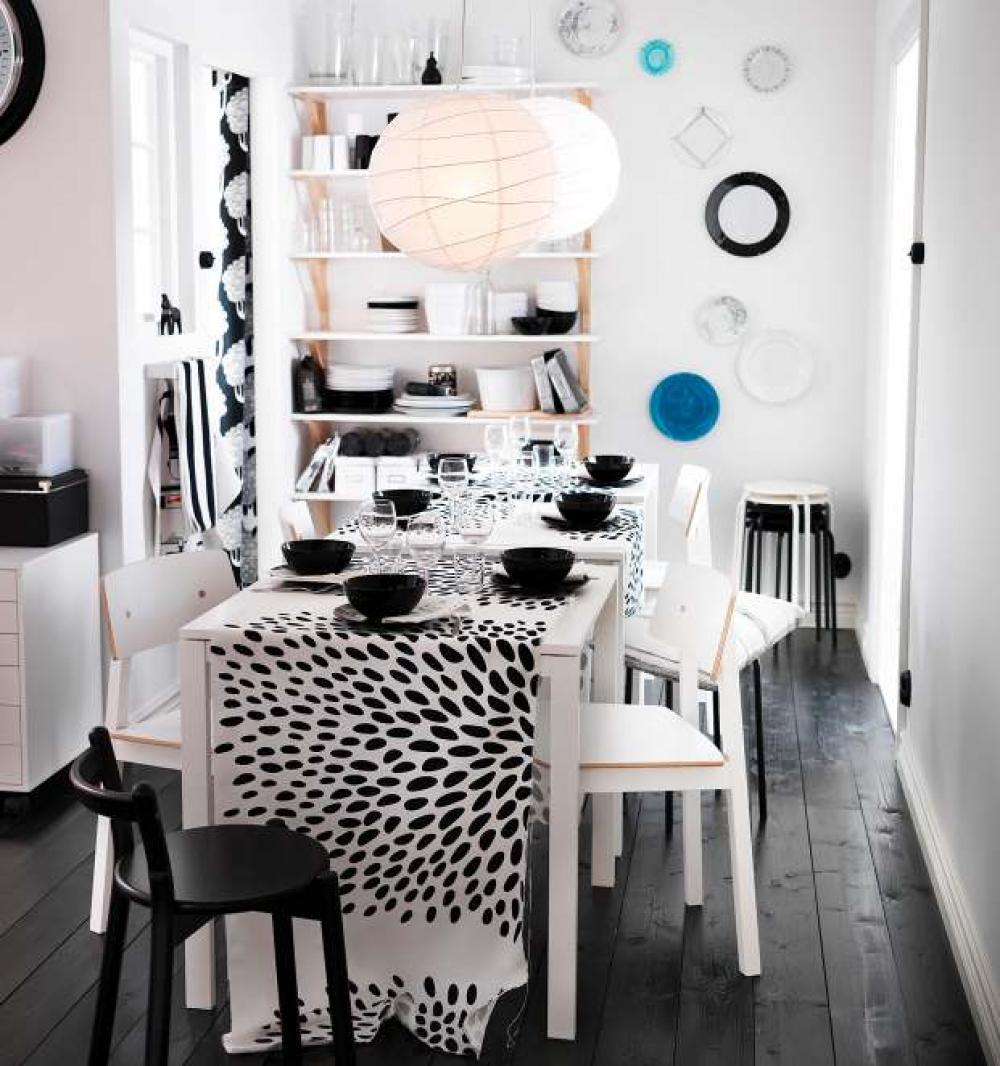 Black and white dining room with white table and chairs, and black and white table cloth