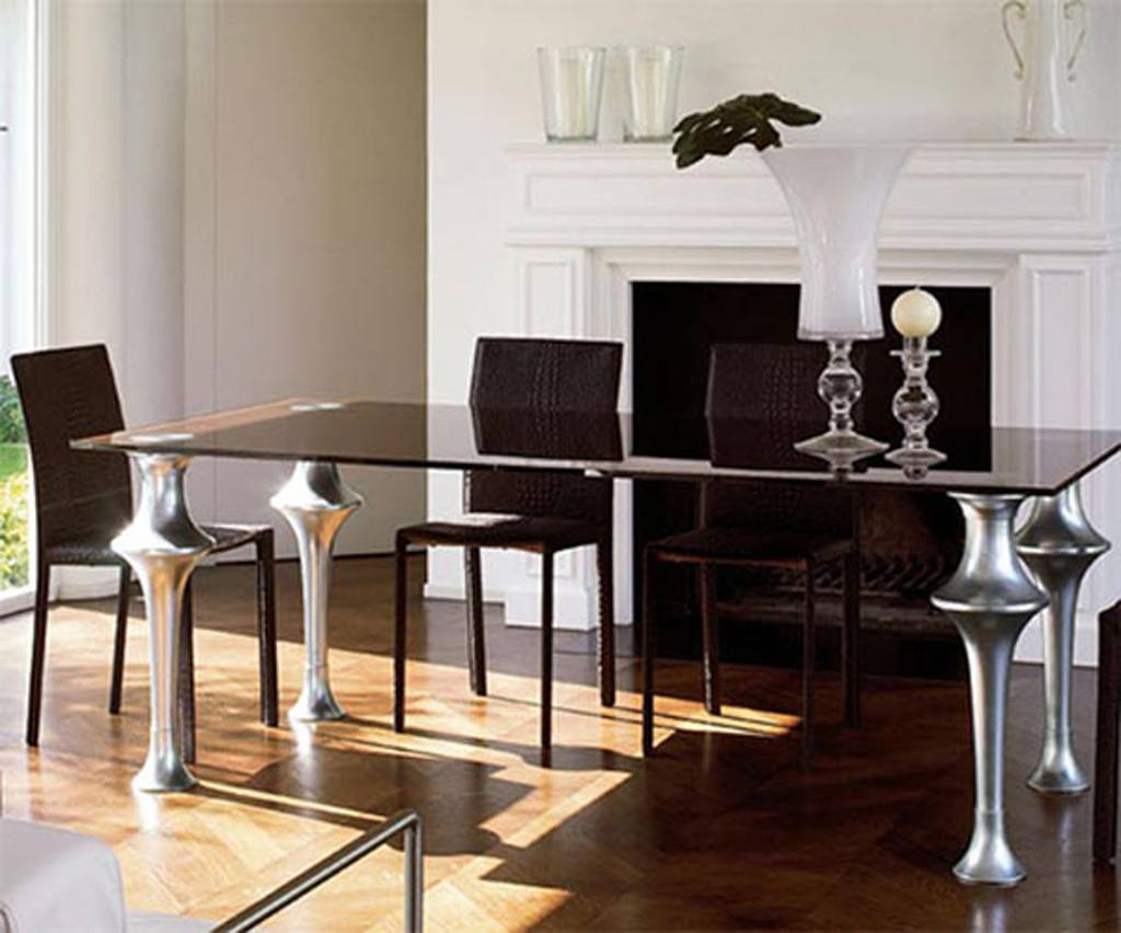 White walled dining room with wooden floors and brown glass reflective table, with round metal legs