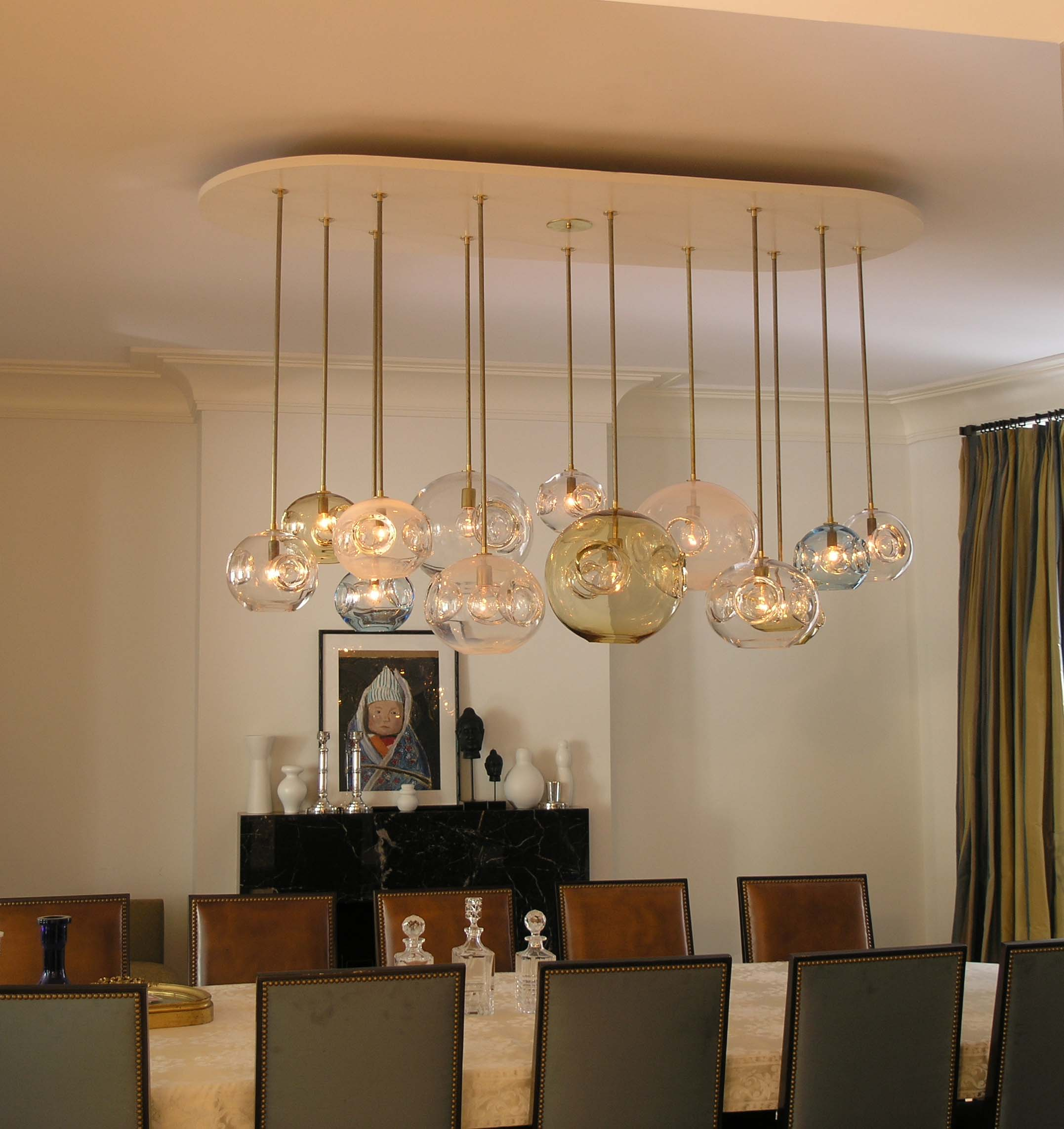 Cream and beige dining toom with round glass light fixtures hanging from the ceiling