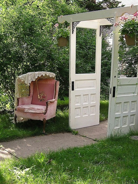 Pink Armchair In The Garden Covered By A Parasol