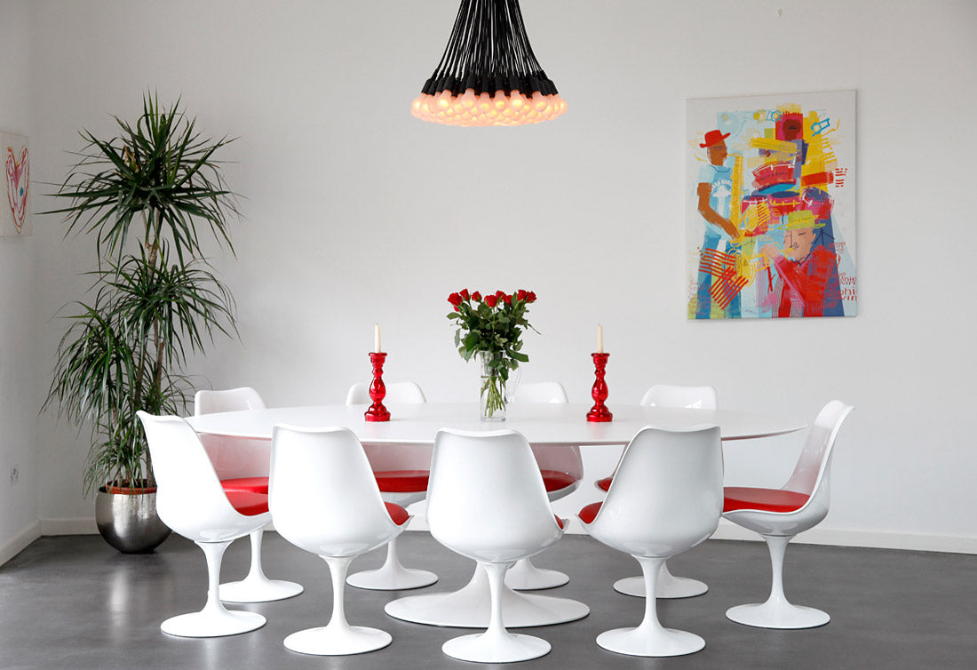 White walled dining room with white table and white chairs with red seat pads, plus red candle holders on the table