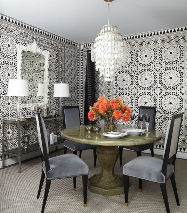 Black and white dining room with disorientating repeat pattern on the walls that looks like doileys or a colour blindness test