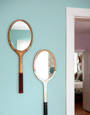Two tennis rackets on the wall with mirrors within frame sections