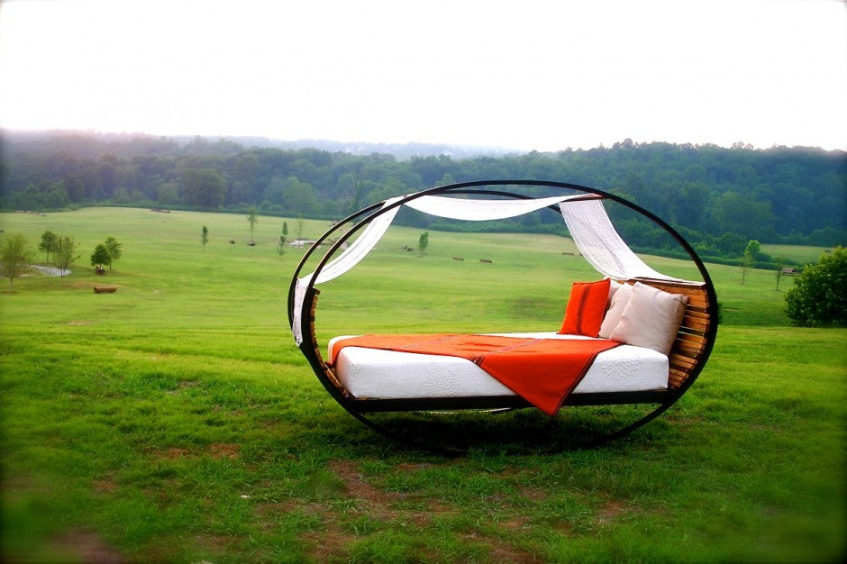 Elliptical Rocking Bed With Orange Bedding, In The Middle Of A Field